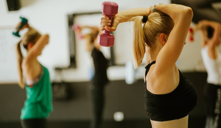 Dobla los codos hacia atrás con las mancuernas para trabajar el tríceps